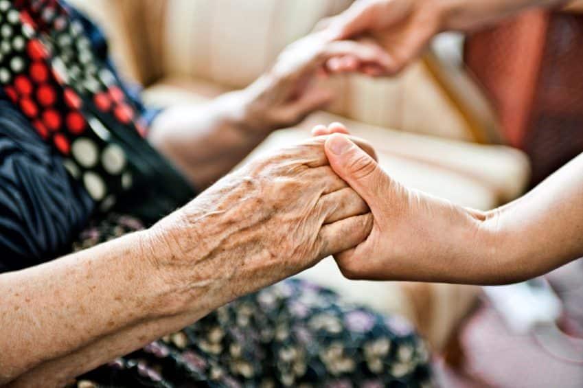 Senior resident holding hands of caregiver